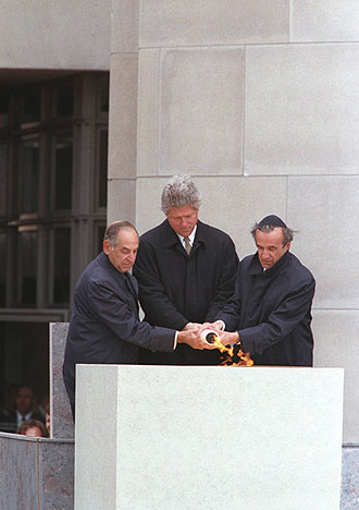 file:/activities/oralhistory/cappics/cohen1945a_flame, alt: President Clinton, Elie Wiesel, and Harvey Meyerhoff lighting an eternal flame