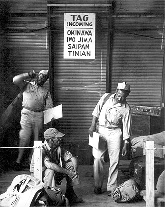 file:/activities/oralhistory/cappics/elliot1939s_okinawa, alt: three african-american soldiers: two standing, one sitting on the ground