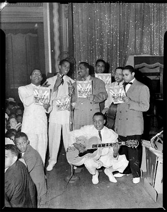 file:/activities/oralhistory/cappics/elliot1939vv_inkspots, alt: 7 african-american musicians holding sheet music with the double V logo on it