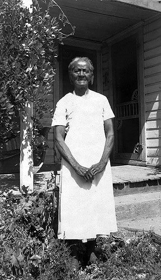 file:/activities/oralhistory/cappics/pryor1923_sarah, alt: B/W photo of Sarah Graves in front of porch