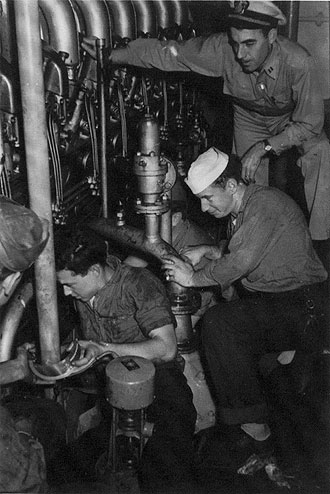 file:/activities/oralhistory/cappics/slater1942_1945_engine, alt: Paul Slater and others working in the engine room of the USS Walter S. Brown